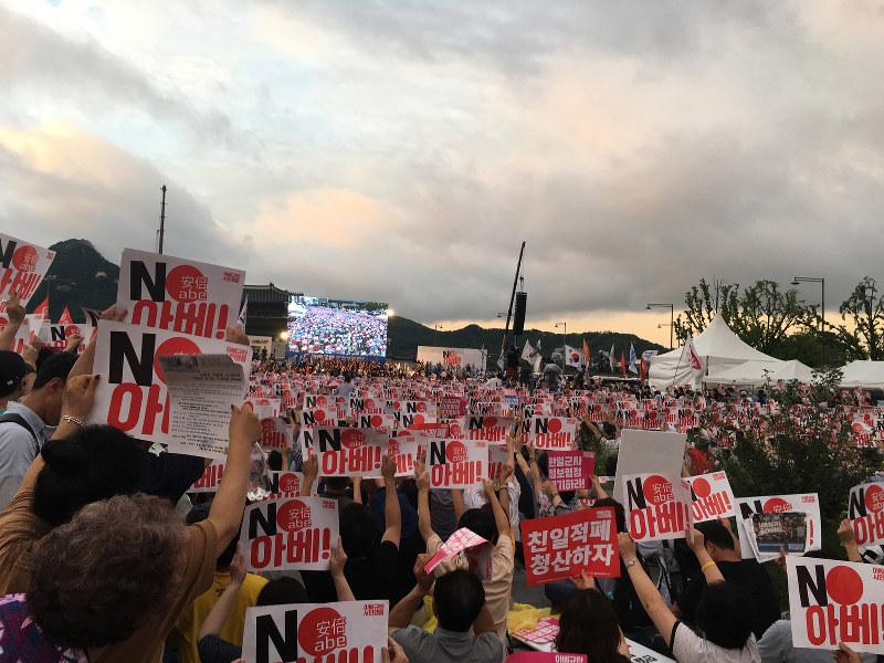 ソウル都心の光化門広場で行われたロウソク集会。参加者は「NO安倍」「親日積弊を清算しよう」というプラカードを掲げた=15日、澤田克己撮影