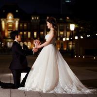 東京駅を背景にポーズを取る夫婦=東京都千代田区で2019年、佐々木順一撮影