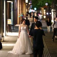 丸の内のオフィス街で結婚写真を撮る夫婦=東京都千代田区で2019年、佐々木順一撮影