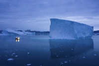 In this Aug. 15, 2019 photo, a boat navigates at night next to large icebergs in eastern Greenland. (AP Photo/Felipe Dana)