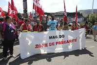 Unionists demonstrate with a banner reading 'Mac Do, social insecurity zone' in front of a McDonald's restaurant, on Aug. 22, 2019 in Hendaye, southwestern France. (AP Photo/Bob Edme)