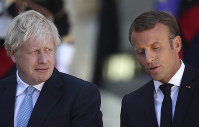 Britain's Prime Minister Boris Johnson looks across at French President Emmanuel Macron at the Elysee Palace, on Aug. 22, 2019 in Paris. (AP Photo/Daniel Cole)