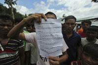 A Rohingya refugee displays to journalists a demand letter about Rohingya repatriation at Nayapara camp in Cox's Bazar, Bangladesh, on Aug.22, 2019. (AP Photo/Mahmud Hossain Opu)