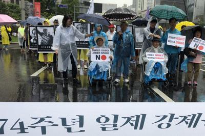 今年の光復節の8月15日、日本に賠償に応じるよう求めデモ行進する徴用工訴訟の原告ら=ソウル市の光化門広場近くで堀山明子撮影