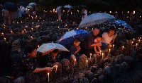 Worshippers are seen offering candles at the thousand light commemoration ceremony at Adashino Nenbutsu-ji temple in Ukyo Ward, Kyoto, on Aug. 23, 2019. (Mainichi/Ai Kawahira)