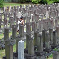 約5000基の墓石が並ぶ旧真田山陸軍墓地。終戦記念日には、手を合わせる男性の姿があった=大阪市天王寺区で2019年8月15日、平川義之撮影