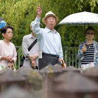 考える会では、その存在を広く知ってほしいと墓地を案内し、歴史を伝えている。吉岡武さん(中央)は墓地の近くに子供の頃から住み、見学会の際は自身の空襲体験を交え、案内する=大阪市天王寺区の旧真田山陸軍墓地で2019年7月14日、平川義之撮影