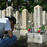 お盆、旧真田山陸軍墓地を家族で訪れ、戦死した親族の墓に花などを供えて、手を合わせる男性。維持会や考える会によると、訪れる人たちは年々減り続けているという=大阪市天王寺区で2019年8月13日、平川義之撮影