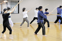 Students are seen practicing their theatrical sword fighting skills at the Mainichi Culture Center in Osaka's Kita Ward on Aug. 11, 2019. (Mainichi/Kenji Konoha)