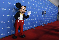 Mickey Mouse waves to members of the media at the Disney Legends press line during the 2019 D23 Expo, on Aug. 23, 2019, in Anaheim, Calif. (Photo by Chris Pizzello/Invision/AP)