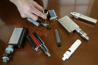 In this April 10, 2018 photo, Marshfield High School Principal Robert Keuther displays vaping devices that were confiscated from students in such places as restrooms or hallways at the school in Marshfield, Mass. (AP Photo/Steven Senne)