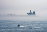 A view of the Grace 1 supertanker is seen through the sea fog, in the British territory of Gibraltar, on Aug. 15, 2019, seized last month in a British Royal Navy operation off Gibraltar. (AP Photo/Marcos Moreno)