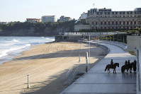 Mounted police officers patrol a beachside area on the first day of the G-7 summit in Biarritz, France, on Aug. 24, 2019. (AP Photo/Markus Schreiber)