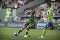 Portland Timbers' Sebastian Blanco strikes the ball next to Seattle Sounders' Cristian Roldan during the first half of an MLS soccer match on Aug. 23, 2019, in Portland, Ore. (Serena Morones/The Canadian Press via AP)