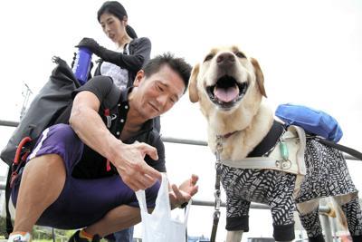 練習場所の西東京スポーツセンターに向かう中沢隆(左)。気温30度の暑さの中、盲導犬のデネブがうれしそうに水を飲んだ=東京都西東京市で、丸山博撮影