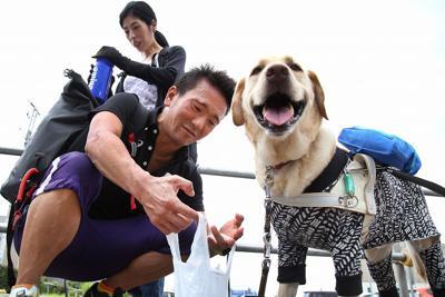 練習場所の西東京スポーツセンターに向かう中沢隆(左)。気温30度の暑さの中、盲導犬のデネブがうれしそうに水を飲んだ=東京都西東京市で2019年6月28日、丸山博撮影