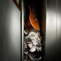 大量の中古の靴とアコースティックギター=大阪市西成区の「冨士屋ロッカー」で、久保玲撮影