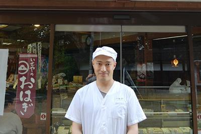 榊莫山さんが書いた「いせや」の看板の下に立つ丸山高さん=三重県伊賀市上野新町で、大西康裕撮影