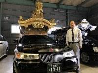Yoshimitsu Araki, president of funeral home Araki, stands beside a Japanese