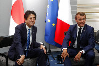 French President Emmanuel Macron attends a bilateral meeting with Japan's Prime Minister Shinzo Abe at the G7 summit in Biarritz, southwestern France, Saturday, Aug. 24, 2019. Shadowed by the threat of global recession, a U.S. trade war with China and the possibility of one against Europe, the posturing by leaders of the G-7 rich democracies began well before they stood together for a summit photo. (Philippe Wojazer/Pool via AP)