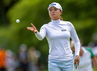 Jin Young Ko, of South Korea, tosses a golf ball to her caddie on the first green during the third round of the CP Women's Open in Aurora, Ontario, Canada, Saturday, Aug. 24, 2019. (Frank Gunn/The Canadian Press via AP)