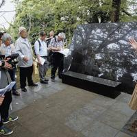 人骨が保管されている石造りの施設を紹介するガイド役の坂本礼奈さん(右)=東京都新宿区で