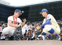 Yasunobu Okugawa of Ishikawa Prefecture's Seiryo High School, right, Taisei Shimizu of Osaka Prefecture's Riseisha High School, put dirt from the pitcher's mound into bags on Aug. 22, 2019, after the closing ceremony of the National High School Baseball Championship at Hanshin Koshien Stadium in Nishinomiya, Hyogo Prefecture. Riseisha claimed its maiden title by defeating Seiryo 5-3 in the final game. (Mainichi/Tatsuro Tamaki)