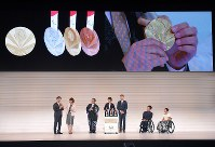 The medals for the 2020 Tokyo Paralympics are revealed during a ceremony to mark one year before the games begin at NHK Hall in Tokyo's Shibuya Ward on Aug. 25, 2019. Medal designer Sakiko Matsumoto is seen in the center. (Mainichi/Koichiro Tezuka)