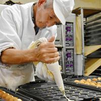 ベビーカステラを焼く星安孝悦さん=三重県名張市上八町の「御菓子司 星安」で、衛藤達生撮影