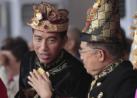 Dressed in traditional outfit, Indonesian President Joko Widodo, left, confers with his deputy Jusuf Kalla during a flag hoisting ceremony commemorating the country's 74th anniversary of independence at Merdeka Palace in Jakarta, Indonesia, on Aug. 17, 2019. (AP Photo/Dita Alangkara)