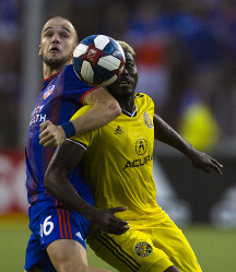 FC Cincinnati defender Andrew Gurman fights for the ball with Columbus Crew forward Gyasi Zerdes (11) in the second half of the MLS soccer match on Aug. 25, 2019, in Cincinnati. (Albert Cesare/The Cincinnati Enquirer via AP)