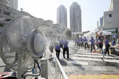 厳しい暑さの中、パラトライアスロンのテスト大会の出場選手に水を手渡すスタッフ。コース沿いには扇風機が設置された=東京都港区で2019年8月17日、佐々木順一撮影