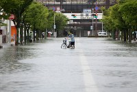 A man pushes his bike on a flooded road in front of JR Saga Station in the city of Saga in the northern Kyushu region on Aug. 28, 2019. (Mainichi/Osamu Sukagawa)