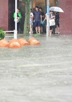 People look at flooded roads from the entrance of a hotel in the city of Saga in the northern Kyushu region on Aug. 28, 2019. (Mainichi/Osamu Sukagawa)