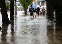People walk along a flooded road in front of JR Saga Station in the city of Saga in the northern Kyushu region on Aug. 28, 2019. (Mainichi/Osamu Sukagawa)