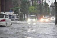 Cars run through a road flooded due to heavy rain in the city of Saga in the northern Kyushu region on Aug. 28, 2019. (Mainichi/Mio Ikeda)