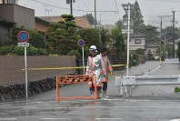 Members of a volunteer fire brigade restrict entry to a flooded road in the city of Kurume, Fukuoka Prefecture, on Aug. 28, 2019. (Mainichi/Shihoko Abe)