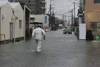 A worker walks through a flooded road to deliver a newspaper in the city of Kurume, Fukuoka Prefecture, on Aug. 28, 2019. (Mainichi/Shihoko Abe)