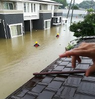 Rescuers move forward through a flooded road while being submerged to their chests in the city of Takeo, Saga Prefecture, in the northern Kyushu region on Aug. 28, 2019. (Photo courtesy of a reader)