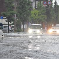 激しい雨により冠水した道路を走る車=佐賀市水ケ江で2019年8月28日午前7時半ごろ、池田美欧撮影