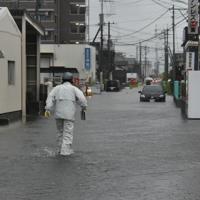 冠水した道を進む新聞を配達する人=福岡県久留米市梅満町で2019年8月28日午前7時15分、安部志帆子撮影