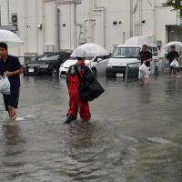 冠水した道を歩く人たち=佐賀市で2019年8月28日午前10時6分、須賀川理撮影