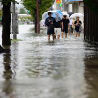 冠水したJR佐賀駅前の道路を歩く人たち=佐賀市で2019年8月28日午前10時32分、須賀川理撮影