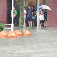 ホテルの入り口で冠水した道路を見つめる人たち=佐賀市で2019年8月28日午前10時8分、須賀川理撮影