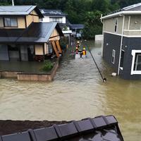 冠水した住宅地でボートを使って救助作業をする消防隊員ら=佐賀県武雄市北方町で2019年8月28日午前8時半ごろ(読者提供)