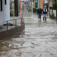 冠水した住宅街を歩く人たち=佐賀県大町町で2019年8月28日午後1時17分、須賀川理撮影