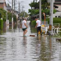大雨の影響で冠水した道路を慎重に歩く住民たち=佐賀県武雄市で2019年8月28日午後4時22分、森園道子撮影