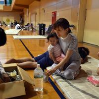 大雨の影響で浸水した自宅から中学校の体育館に避難し、食事の支援を受ける住民たち=佐賀県武雄市で2019年8月28日午後6時34分、森園道子撮影
