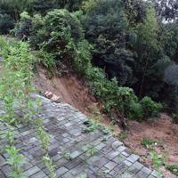 大雨の影響で民家の庭が大きく崩れ、下方の民家(右下)に迫った=佐賀県武雄市で2019年8月28日午後5時36分、森園道子撮影