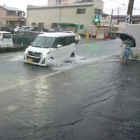 冠水した道路を水しぶきをあげて走る車=佐賀市大財で2019年8月28日午前7時半、光田宗義撮影